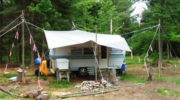 Click to enlarge.  June 10, 2009.  I didn't have that fancy store-bought canopy.  I made my own.  It went up every spring and down every fall from 2005 to 2009.  I didn't bother in 2010 because the house showed up that June.  The tarp is still in great shape, and it went through some really nasty storms with ZERO problems.  The secret is guy lines and bungee cord shock absorbers to cushion the strain on the grommets.  None of the poles are IN the ground.  Just tied down with three stakes around the base of each.  I still have most of the poles (maple).  Never know when a nice hunk of maybe will come in handy.  Now you really know how goofy I am.Note there once was 300 ft. of forest between the camper and the road before the house came.